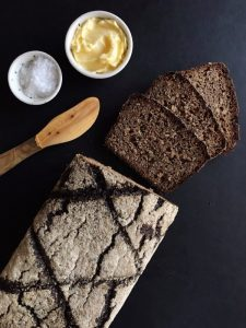 Vollkornbrot loaf with spreading knife, butter, and salt
