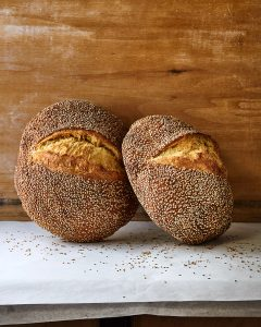 Two loaves of Sesame Semolina leaning against a wooden wall