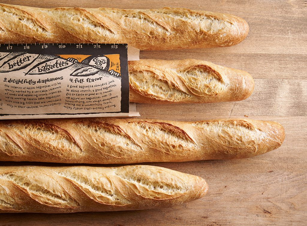 Four French baguettes, one in a paper bag