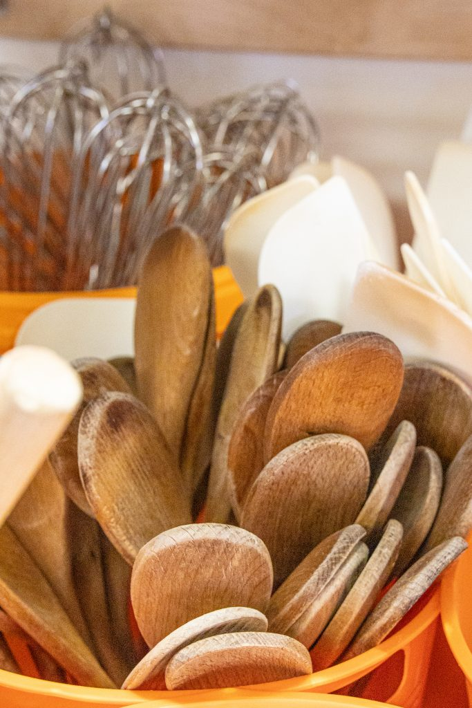 wooden spoons in an orange plastic container