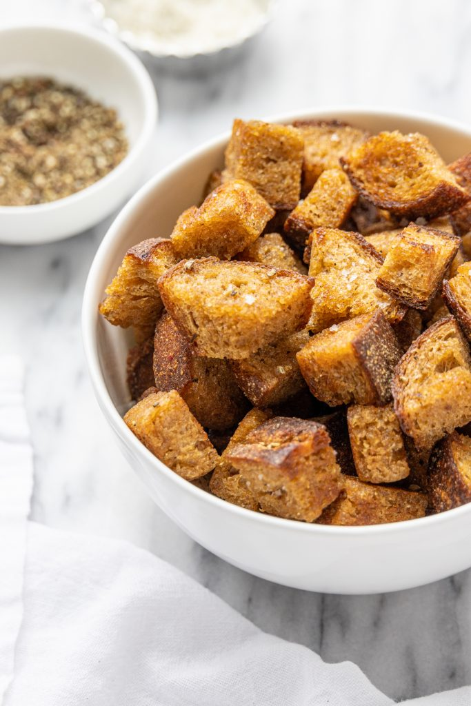 croutons in a white bowl on a marble table