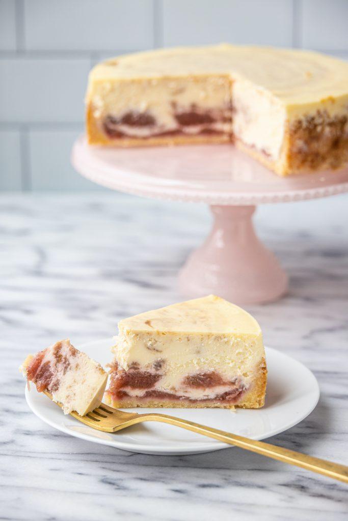 rhubarb cheesecake on a pink cake stand