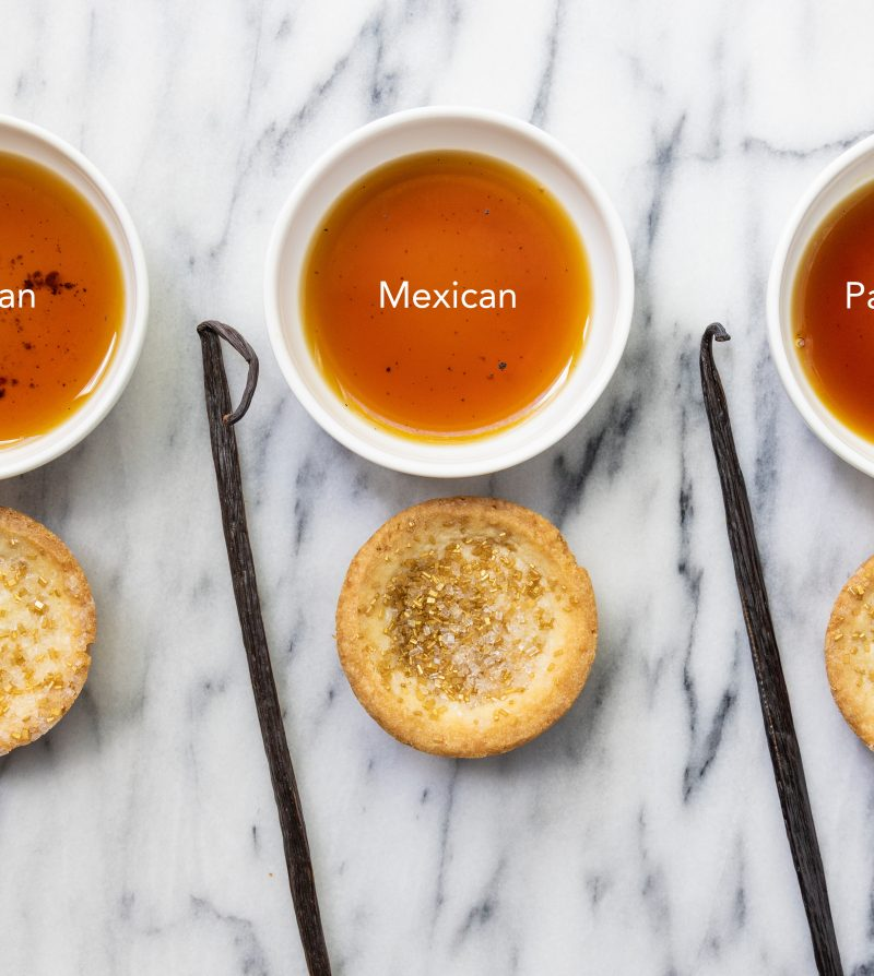 three small white dishes with vanilla extract, each paired with a vanilla bean and a cookie